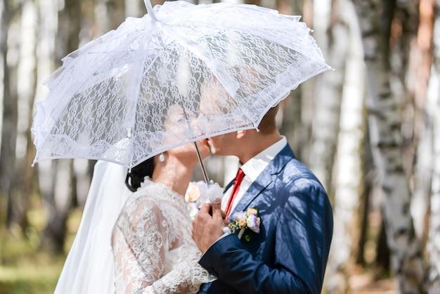 Narzeczeni całowanie pod parasolem w parku.