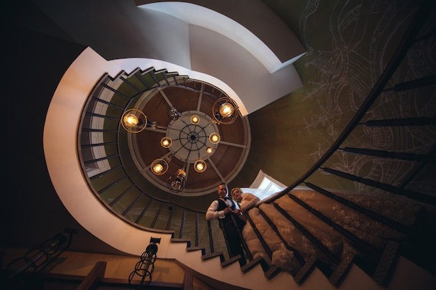 Narzeczeni całują się i przytulają na spiralnych schodach. portret kochających nowożeńców w pięknym wnętrzu. dzień ślubu. koncepcja ślubu. właśnie wyszła za mąż. ślub para zakochanych wewnątrz