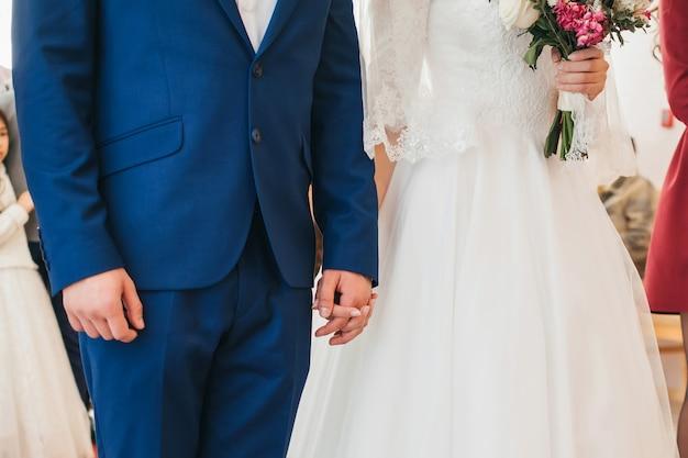 Narzeczeni na ceremonii ślubnej, trzymając się za ręce