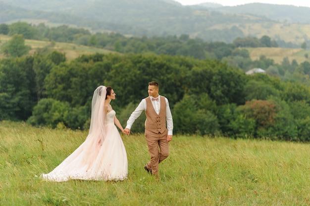 Narzeczeni na spacerze weselnym. kochająca para patrzy sobie w oczy. pan młody prowadzi swoją narzeczoną wzdłuż zielonej łąki na tle lasu. miejsce na logo.