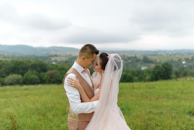 Narzeczeni na spacerze weselnym. kochająca para przytula się i patrzy sobie w oczy. ścieśniać.