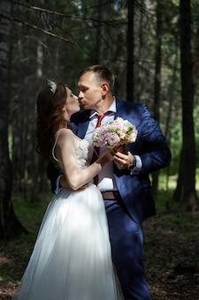 Narzeczeni obejmują i całują w ciemnym lesie w słońcu. ślub w naturze, portret zakochanej pary w parku