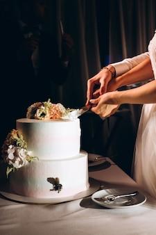Narzeczeni pokroić tort weselny. białe ciasto ozdobione świeżymi kwiatami. luksusowy deser ślubny.