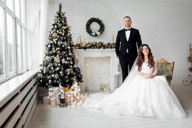 Narzeczeni pozowanie w studio na tle ozdobione choinką w dniu ślubu