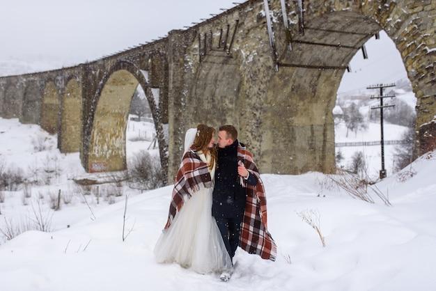 Narzeczeni przytulają się pod dywanikiem, aby się ogrzać. zimowe wesele