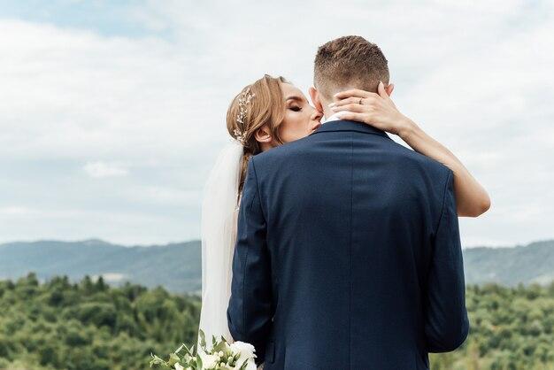 Narzeczeni przytulanie na weselu w przyrodzie