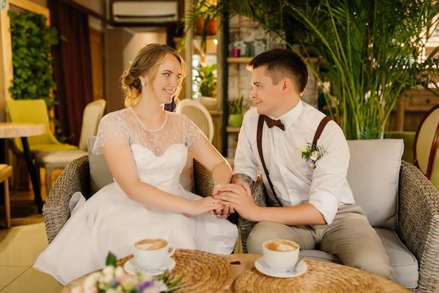 Narzeczeni siedzą w przytulnym wnętrzu, trzymając się za ręce i patrząc na siebie. koncepcja ślubu.