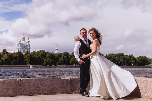 Narzeczeni stoją na rzece i katedrze. nowożeńcy w sukniach ślubnych w słoneczny dzień ślubu