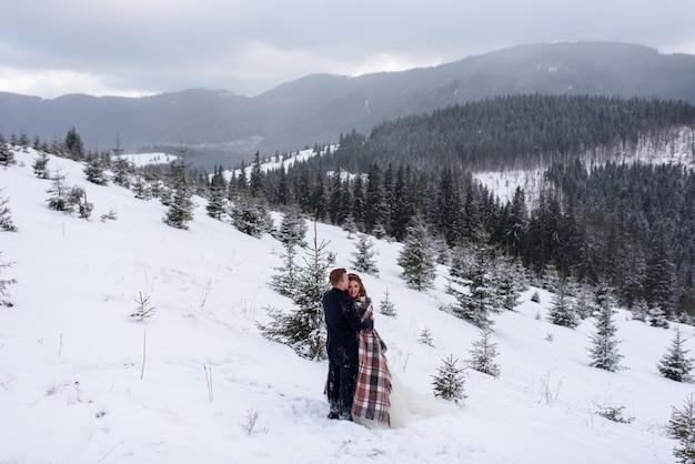 Narzeczeni stoją na tle gór i przytulają się pod dywanikiem, aby się ogrzać. zimowe wesele