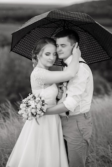 Narzeczeni stoją na tle pięknego krajobrazu z parasolem.