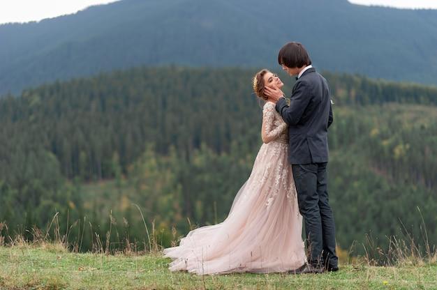 Narzeczeni świętują ślub w górach. fotografia ślubna. ceremonia ślubna dla dwojga.