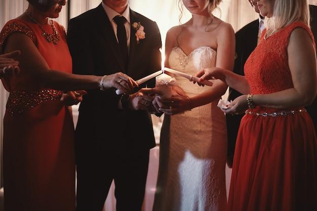 Narzeczeni trzymają płonącą świecę rodzinną w dniu ślubu po ceremonii. tradycje i zwyczaje.
