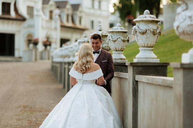 Narzeczeni w dzień ślubu chodzenie na zewnątrz na wiosnę natura. pary młodej, szczęśliwa nowożeńcy kobieta i mężczyzna w zielonym parku. kochająca ślub para plenerowa.