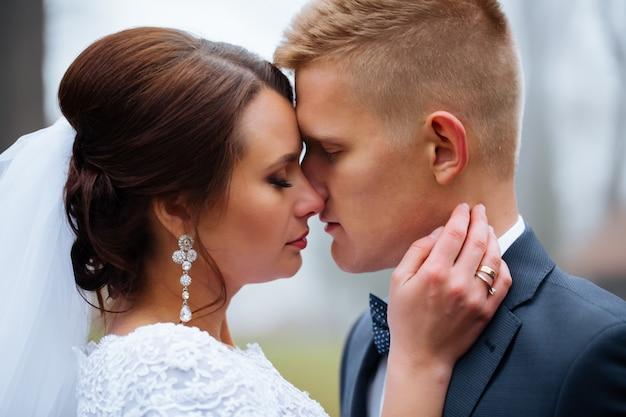 Narzeczeni w dzień ślubu na zewnątrz. nowożeńcy mężczyzna i kobieta. szczęśliwa para w dzień ślubu. śmieszne szczegóły ślubu. miękka tonacja