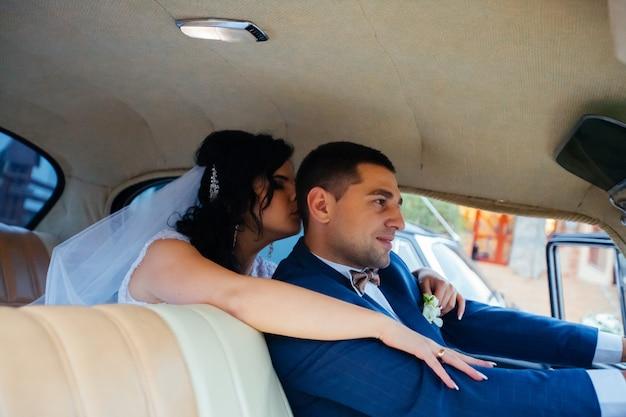 Narzeczeni w klasycznym samochodzie. oni są szczęśliwi.