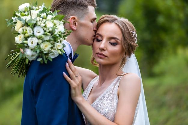 Narzeczeni w parku całowanie. para nowożeńców narzeczeni na weselu w przyrodzie zielony las całują portret portret. para młoda