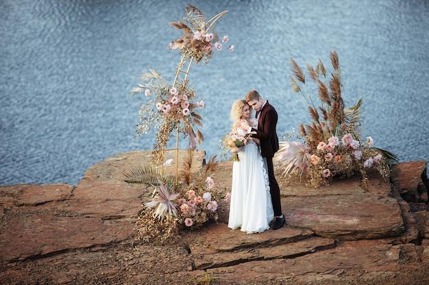 Narzeczeni w pobliżu dekoracji ślubnej podczas ceremonii na klifie w pobliżu wody o zachodzie słońca