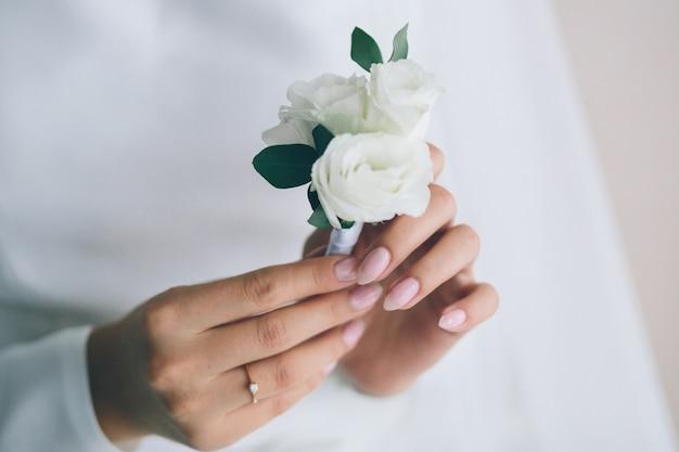 Narzeczonych trzymając się za ręce butonierki. kobieta w pięknej białej sukni. preparaty narzeczonych. ślub.