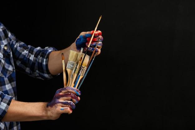 Narzędzia artysty. asortyment pędzli w rękach człowieka rozmazanych farbą. hobby sztuki. zajęcie procesu twórczego.