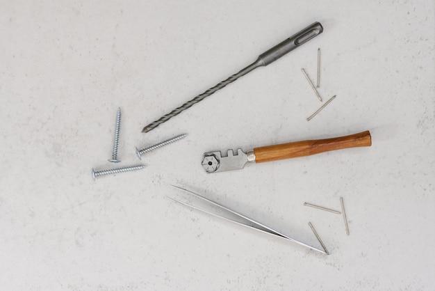 Narzędzia budowlane: nóż do szkła z drewnianym uchwytem, wiertło do dziurkacza, pincety, gwoździe i śruby na jasnym tle