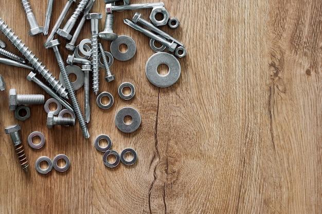 Narzędzia budowlane. śruby, nakrętki i śruby na podłoże drewniane. naprawa, koncepcja poprawy domu. wolne miejsce na tekst, widok z góry, układ płaski.