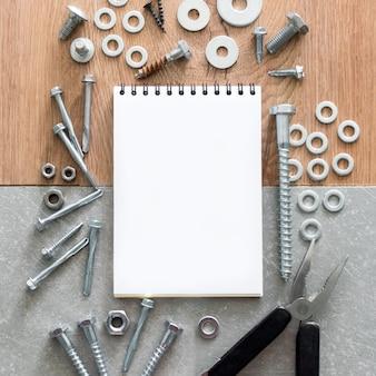 Narzędzia budowlane śruby nakrętki i śruby ułożone wokół pustego papieru zeszytowego w spirali