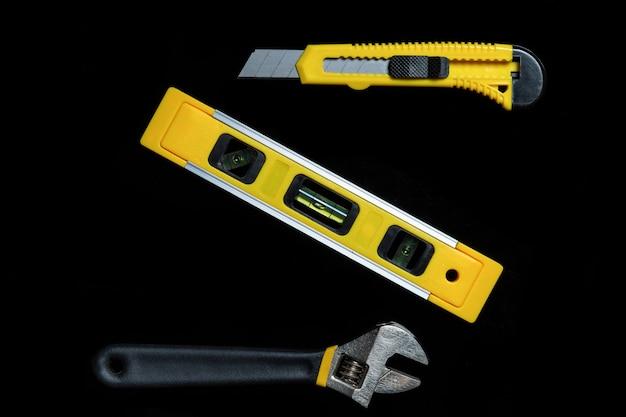 Narzędzia dla głównego konstruktora na czarnym tle. zamknij się narzędzie budowlane. widok z góry