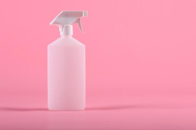 Narzędzia do czyszczenia. butelka z rozpylaczem na białym tle na różowym tle.
