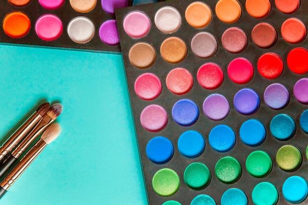 Narzędzia do makijażu i kosmetyki różne odcienie palety cieni do powiek i pędzel do makijażu na modnym, kolorowym, pastelowym, niebieskim tle
