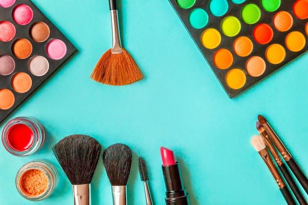 Narzędzia do makijażu i kosmetyki różne odcienie palety cieni do powiek oraz pędzel do makijażu na modnej kolorowej niebieskiej paście