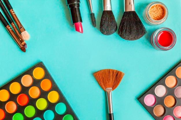 Narzędzia do makijażu i kosmetyki różne odcienie palety cieni do powiek oraz pędzel do makijażu na modnym, kolorowym niebieskim pastelowym kolorze