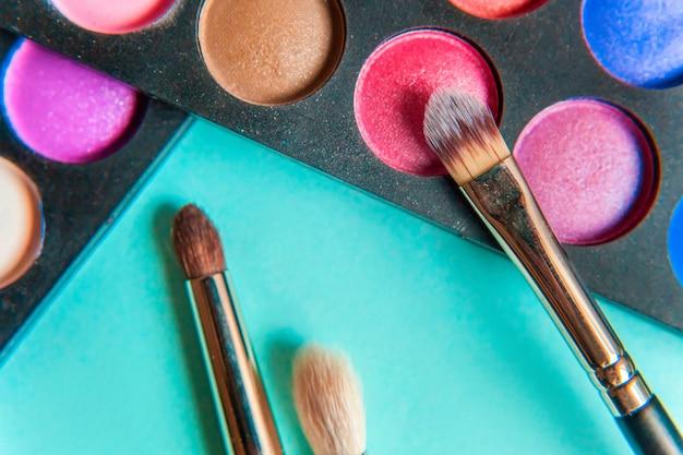 Narzędzia do makijażu i kosmetyki różne odcienie palety cieni do powiek oraz pędzel do makijażu na modnym, kolorowym, pastelowym, niebieskim stole. widok z góry na płasko