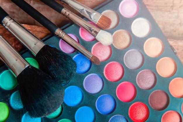 Narzędzia do makijażu i kosmetyków paleta i makijaż pędzel na rustykalne stare drewniane tła