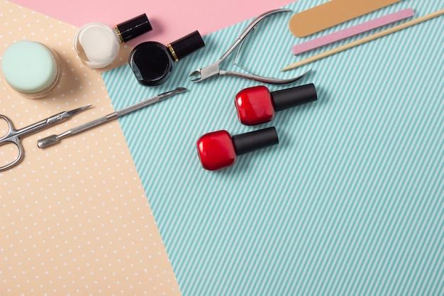 Narzędzia do manicure na różowym i niebieskim tle.