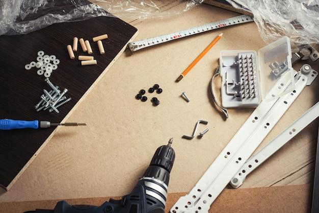 Narzędzia do montażu mebli, detale mebli, folia do pakowania, śruby na kartonie. warsztat koncepcyjny