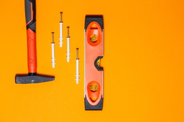 Narzędzia do naprawy. młotek do gwoździ, poziom, kołek w ścianie na pomarańczowym tle. zestaw narzędzi dla kreatora