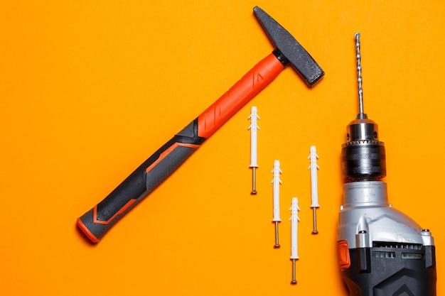 Narzędzia do naprawy. młotek do gwoździ, wiertło, kołek w ścianie na pomarańczowym tle. zestaw narzędzi dla kreatora