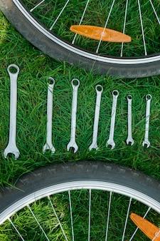 Narzędzia do naprawy roweru na trawie między kołami.