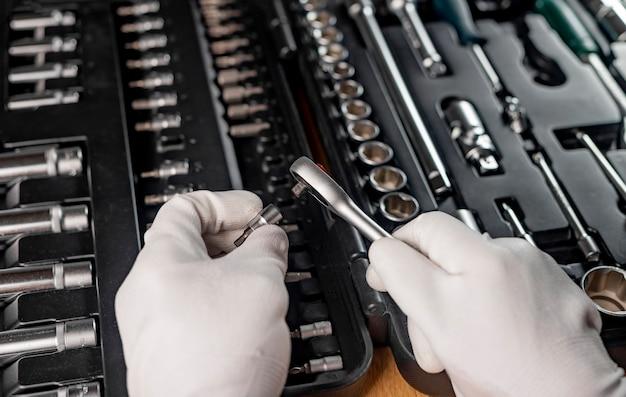 Narzędzia do naprawy samochodów w męskich rękach z bliska