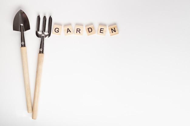 Narzędzia do ogrodnictwa w domu i napis ogród wykonany z drewnianej kostki