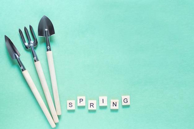 Narzędzia do ogrodnictwa w domu i wiosenny tekst wykonany z drewnianej kostki