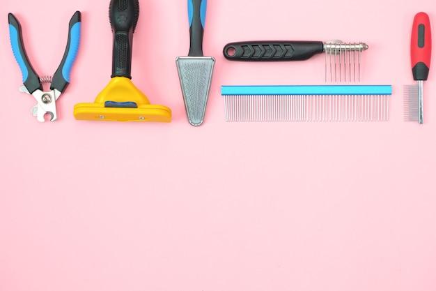 Narzędzia do pielęgnacji i pielęgnacji zwierząt domowych na różowym tle. koncepcja opieki i higieny dla zwierząt. skopiuj miejsce, miejsce na twój tekst. makieta