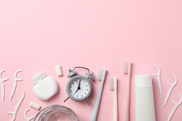 Narzędzia do pielęgnacji zębów na różowym tle, widok z góry