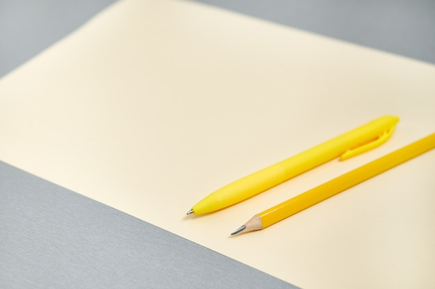 Narzędzia do pisania i rysowania na szarej powierzchni. połączenie kolorów żółtego i szarego.