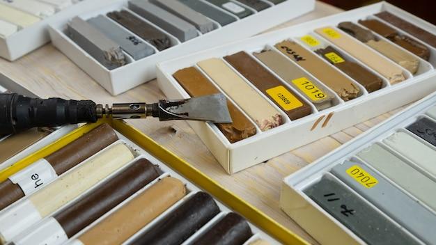 Narzędzia do renowacji powierzchni drewnianych, zestaw ołówków woskowych oraz lutownica do naprawy zarysowań.