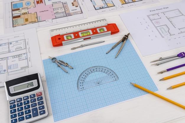 Narzędzia do rysowania z projektami domów i papierem milimetrowym