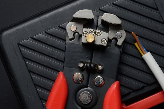 Narzędzia do ściągania izolacji i odizolowany drut spoczywają na skrzynce narzędziowej. zbliżenie.