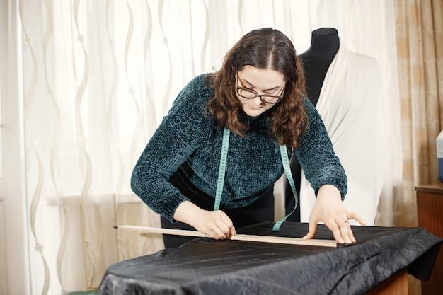 Narzędzia do szycia ubrań. kobieta i okulary. krawcowa z centymetrem na ubrania