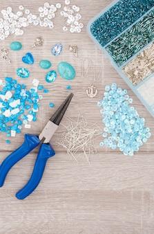 Narzędzia do wyrobu biżuterii. kryształy, wisiorki, uroki, szczypce, szklane serca, pudełko z koralikami i akcesoria na starym drewnianym tle.