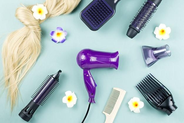 Narzędzia fryzjerskie i przedłużanie włosów na niebieskim drewnianym